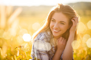 white woman smiling in a sunlit field, general dentistry cinco ranch tx, about lovett dental cinco ranch