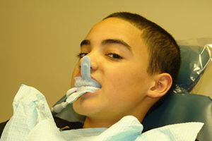 boy being operated on in dentist chair, fluoride treatments tx