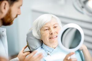woman looking at her new dentures in a mirror
