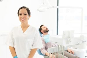 dentist with patient in background getting preventative dentistry